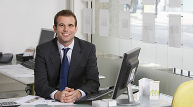 a similing young man in business suit sitting in an office